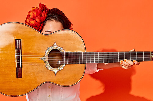 A woman holding a guitar in front of her face. The background is orange and she has a large orange flower in her hair.