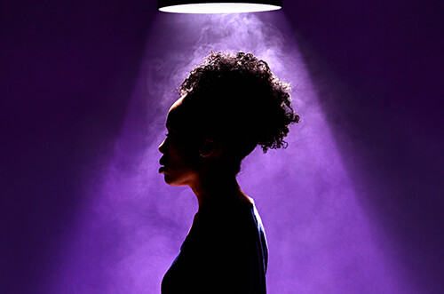 A woman has her profile turned to us and above her head a bright spotlight shines down